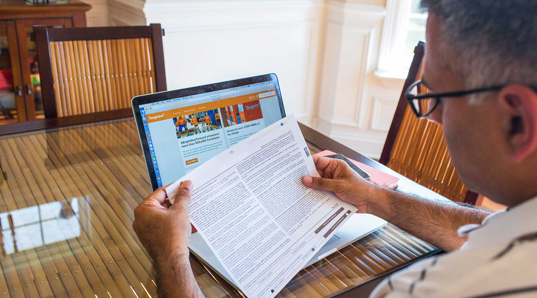 Image of man sitting at a table with his laptop open reading a form.